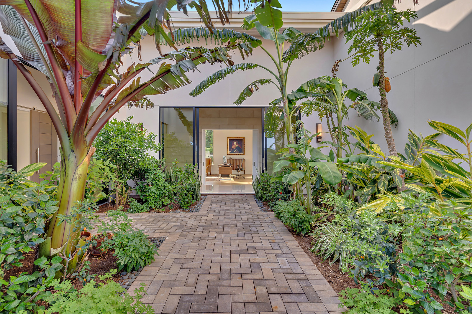 Tropical courtyard with retractible roof and wall and producing plants